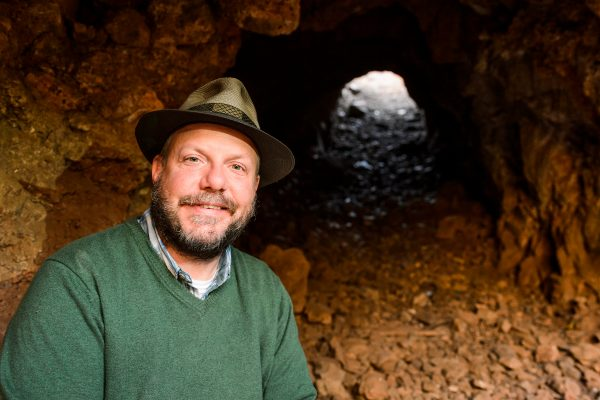 John Hawks poses in front of a cave.