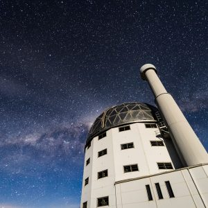 A nighttime long exposure of Southern African Large Telescope showing a sky filled with stars and the Milky Way Galaxy.