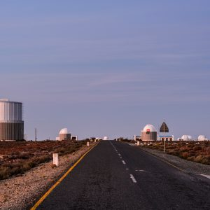 The paved road to the Southern African Large Telescope, showing smaller dome shaped structures and little vegetation around them. Big blue sky.