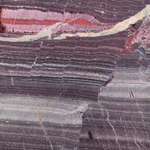 Rock sample from the Barberton core showing a closeup of orange and dark red striations