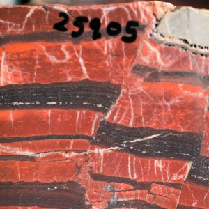 Closeup of rock specimen with dark red and brown layers