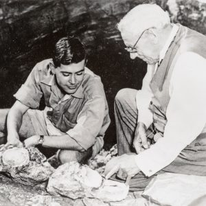 Historical black and white photo of John Robinson (student) and Robert Broom (teacher) at the mouth of a cave.