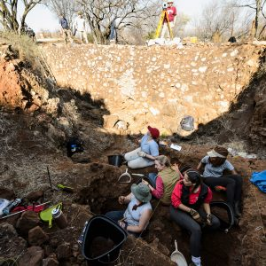 Five field school students at the bottom of a shallow archaeological site digging on a bright day.