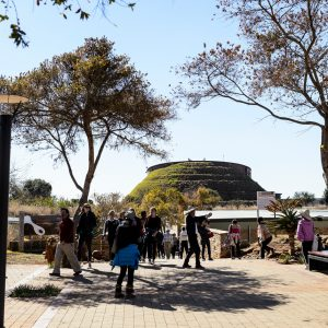 Exterior view of the Maropeng Museum in South Africa, a mounded structure in the background, visitors milling in the foreground on a bright day.