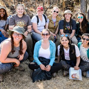 Group shot of 10 smiling female students posing outdoors in South Africa.